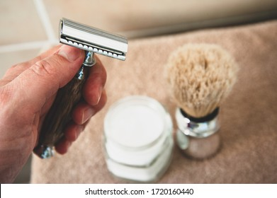 Close-up of safety razor 50s style and male cosmetic products and supplies used by men to shave. Safety razor, shaving brush and foam on beige towel background. Eco friendly tools for men shaving.