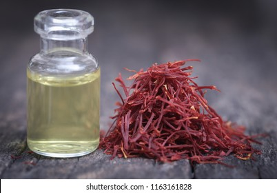 Closeup of Saffron with extract in a bottle on natural surface