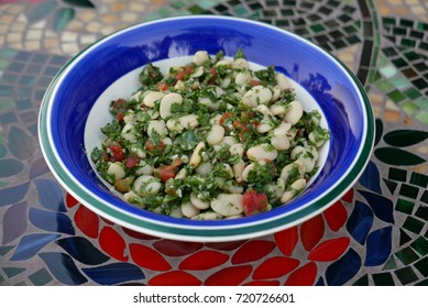 Closeup of salad with white beans and herbs on a plate with blue and green rim  on a table with a mosaic pattern