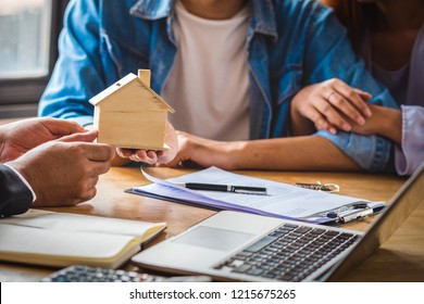 Closeup Sale representative hand offer the wooden house mockup to Asian couple after signed contact estate purchase or rental on the working space table in new place,Moving and House Hunting concept