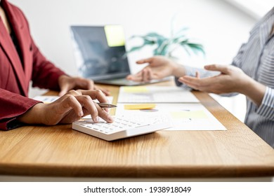 A close-up of the sales manager pressing the white calculator, she is examining the sales figures with management to summarize the monthly results and joint planning. Sales management concept.
