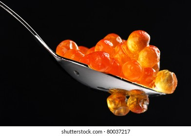 Close-up of salmon caviar with spoon on black background.