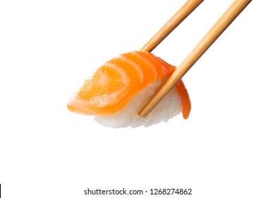 Closeup of salmon nigiri held with bamboo chopsticks. Fresh sushi nigiri isolated on white background. Eating sushi at restaurant. Japanese cuisine with rice and raw fish.