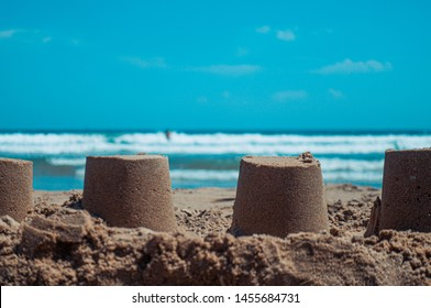 Closeup of sandcastles on the sand of a beach, with the mediterranean sea in the background. Summer and vacations concept.
