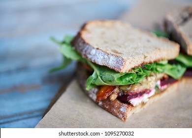 Closeup of a sandwich with assorted organic vegetables cut in half and resting on a piece of paper and board on a wooden table