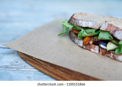 Closeup of a sandwich with assorted organic vegetables resting on a piece of paper and board on a wooden table