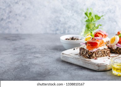 Close-up of sandwich with dark rye bread, cream cheese, salmon, onion, boiled egg on white wooden cutting board, concrete background. Traditional Scandinavian open sandwich Smorrebrod, space for text