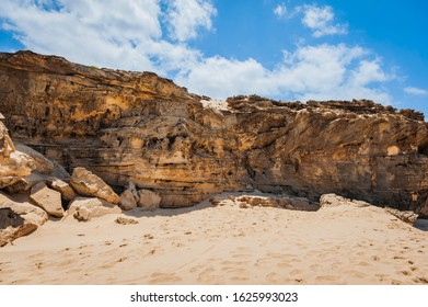 Closeup of sandy rock cliff eroded by wind and water of Atlantic Ocean. The West coast of Boa Vista island, Cape Verde.