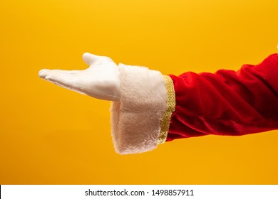 Close-up of Santa Claus gloved hand show giving gesturing on yellow background. Festive time for happy New Year, Merry Christmas, traditional seasonal celebration.