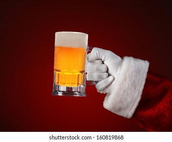 Closeup of Santa Claus holding a mug of beer. Horizontal format on a light to dark red spot background.