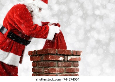 Closeup of Santa Claus placing his bag inside a chimney. Horizontal with copy space over a light bokeh background and snow effect.