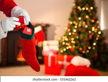 Close-up of Santa Claus putting gift boxes in Christmas stocking