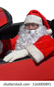 Closeup of Santa sitting behind the wheel of a red sports car.