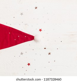 Closeup of Santa's red hat on old white wooden background with shinny silver stars. Christmas, winter and holidays season concept.