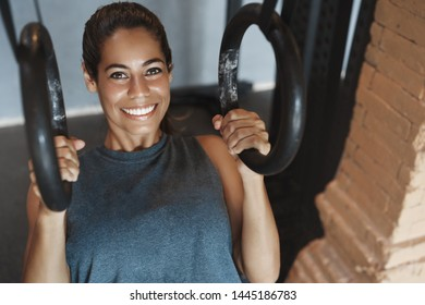 Close-up satisfied sweaty attractive smiling woman doing crossfit gymnastic rings exercise push-ups, look motivated delighted, wear activewear, training session alone in gym, train muscles