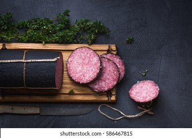 Closeup sausage, sliced on the black coated Board with herbs, thyme, rosemary. Vintage knife, vintage cutting Board.