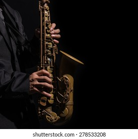 Closeup saxophone in player action on a dark background