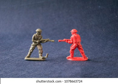 Close-up of scale models of red and green plastic military men battle scene. They standing facing each other and attack at war. Isolated on dark background
