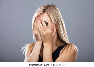 Close-up Of A Scared Woman Peeking Through Fingers