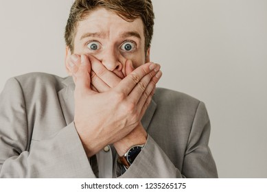 Close-up of scared young man covering mouth with hands. Shocked expressive businessman in gray suit looking astonished. Receiving news concept