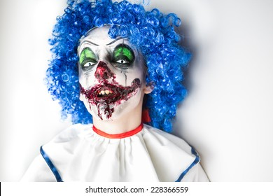 A closeup of a scarier clown with sharp pointy teeth glaring at you. Crazy ugly grunge evil clown on Halloween. Scary professional Halloween masks
