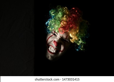 Close-up of a scary clown peeping around the corner of a black wall. He is wearing a colored wig and sharp fangs.