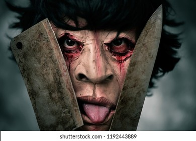 closeup of a scary disfigured man holding a rusty and bloody cleaver and a rusty and bloody knife in front of his face, while sticking his tongue out