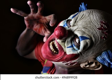 closeup of a scary evil clown against a black background