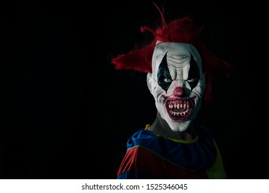 closeup of a scary evil clown with red hair, white eyes, bloody teeth and a threatening look staring at the observer, against a black background with some blank space