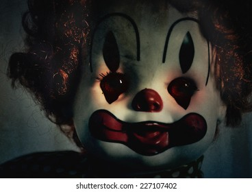 A closeup of a scary evil clown toy doll that could be possessed with evil. Use it for a halloween or fear concept.
