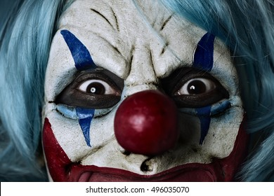 closeup of a scary evil clown wearing a blue hair wig