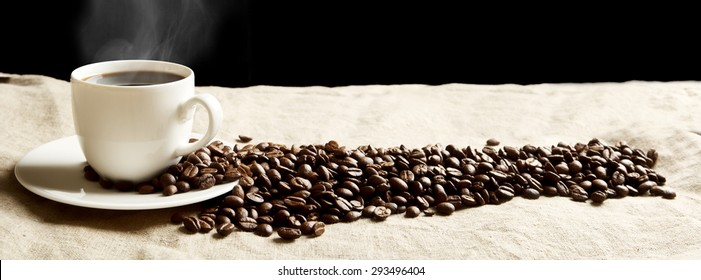 Closeup scattered coffee cup with foam and plenty beans in panoramic view on fabric linen