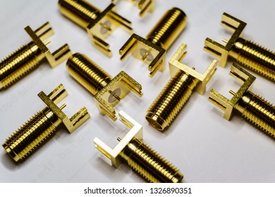 Close-up of scattered gold plated SMA male connectors electronics components on white background in random pattern