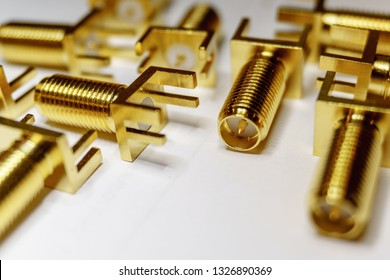 Close-up of scattered gold plated SMA male connectors electronics components in partial focus on white background in random pattern