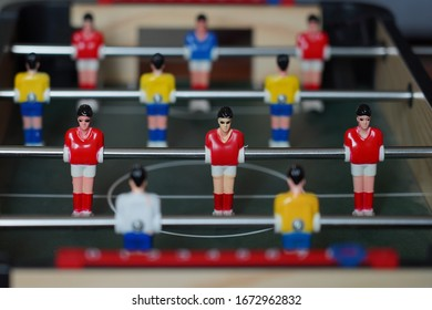 Closeup scene on table football player dolls in red and yellow shirts.