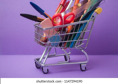 closeup of school supplies in supermarket mini trolley on purple background