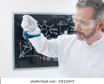 close-up of a scientist in a chemistry lab analyzing colorful substances around laboratory tools and  with a blackboard on the background