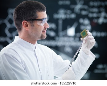 close-up of scientist in a chemistry lab holding in hands and analyzing a hard disk and a blackboard on the background