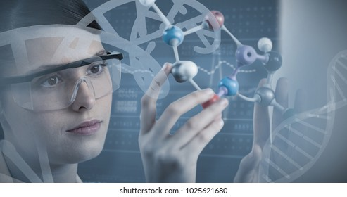 Close-up of scientist holding molecular model against panoramic view of information data on device screen