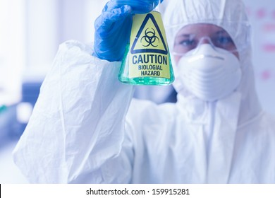 Close-up of a scientist in protective suit with hazardous blue chemical in flask at the laboratory