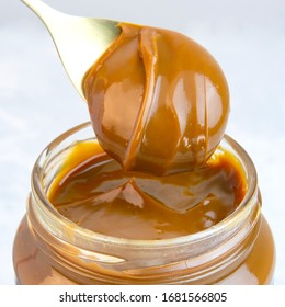 Close-up of scoop and jar full of dulce de leche or dulce de leche