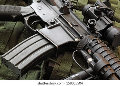 Close-up of a scratched M4A1 (AR-15) carbine and green military tactical vest