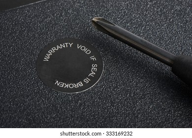 closeup of screwdriver and warranty seal on a laptop computer. Most electronics has the warranty seal and the warranty void If the seal is removed or broken.