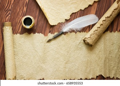 Closeup of scroll and quill near ink-pot on wooden table