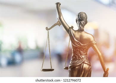 Closeup of a sculpture of Themis, mythological Greek goddess, symbol of justice, blind and holding empty balance in her hand