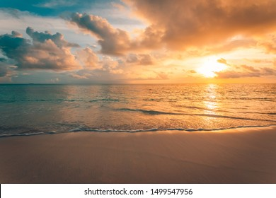 Closeup of sea beach and colorful sunset sky. Panoramic beach landscape. Empty tropical beach and seascape. Orange and golden sunset sky, soft sand, calmness, tranquil relaxing sunlight, summer mood
