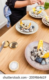Closeup of seafood canape ready to eat on the table. Female cook preparing the dinner. Banana chifles with fake squid noodles and beluga caviar on wooden table served for lunch. Delicatessen food.