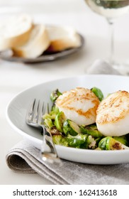 Closeup of seared scallops with roasted Brussels sprouts and nuts.