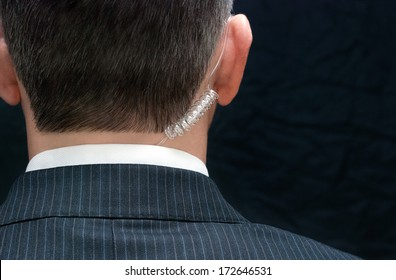 Close-up of a secret service agent, behind.