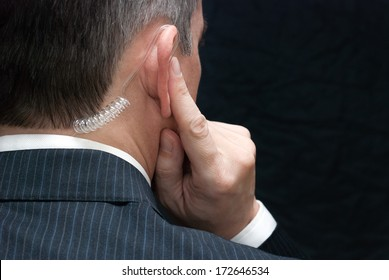 Close-up of a secret service agent listening to his earpiece, over the shoulder.